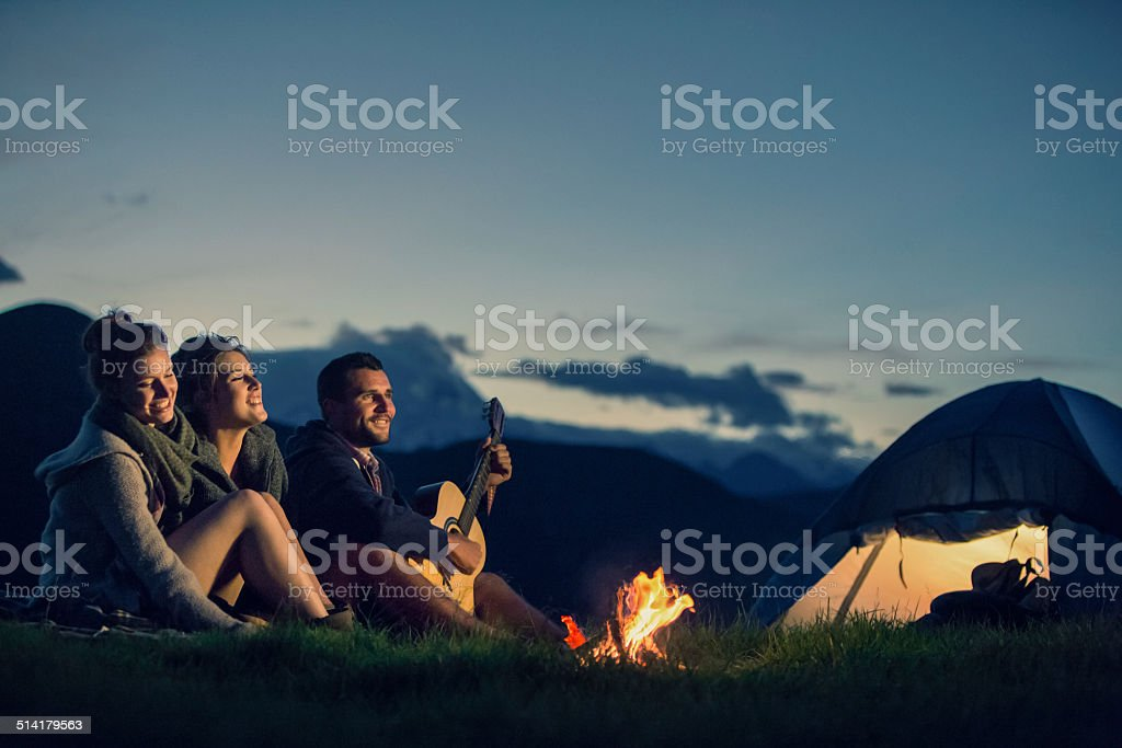 Three friends camping with guitar singing on mountain at night stock photo