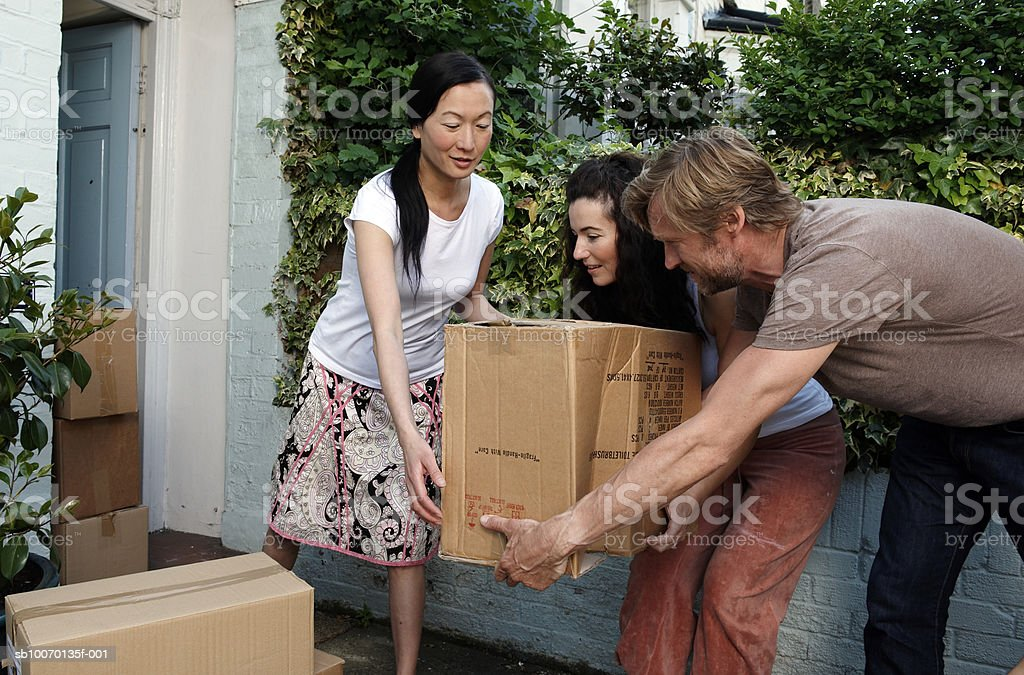 Three friends carrying cardboard boxes outside house royalty free stockfoto