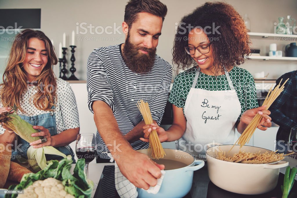 Three friends cooking spaghetti stock photo