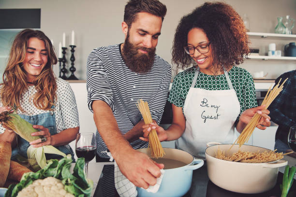 three friends cooking spaghetti - home cooking stock photos and pictures