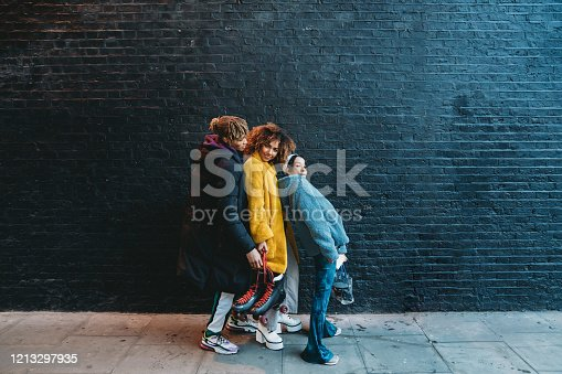Three friends dancing in the city against a black brick wall. African and mixed race ethnicities. They are having fun together.