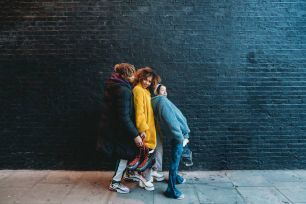 three friends dancing in the city against a black brick wall - pics for cool girl stock pictures, royalty-free photos & images
