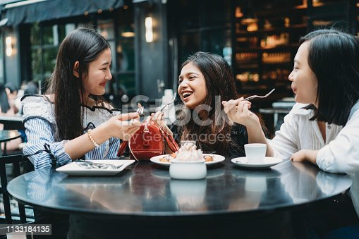 Three friends eating a dessert at the restaurant together
