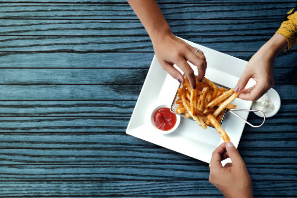 three friends eating french potato fries, serve on metal mesh flying sieve with two dipping sauce. lay on wooden table. high angle top view shot - patatine foto e immagini stock