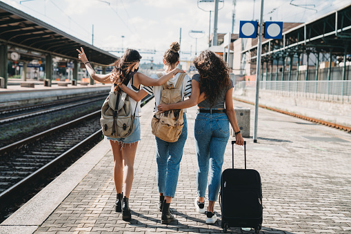 Three friends enjoying a trip together - Rear view. They are at a railroad train station.