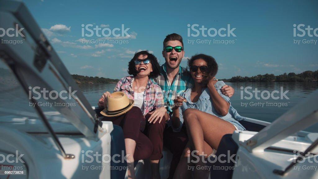 Three friends having fun on boat stock photo