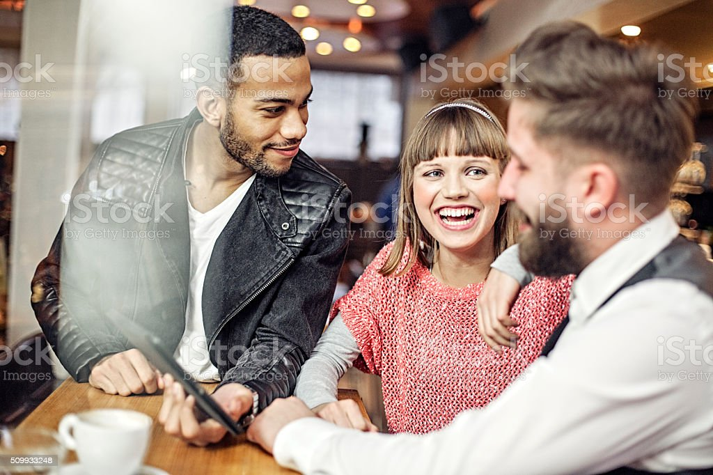 Three friends in a bar with drinks using digital tablet stock photo