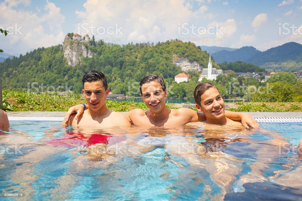 three friends in a swimming pool in Europe stock photo