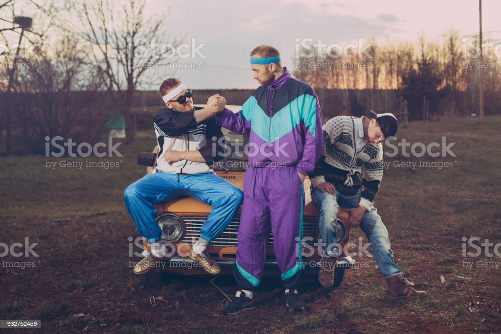 Three friends in the style of the nineties are about orange old car stock photo