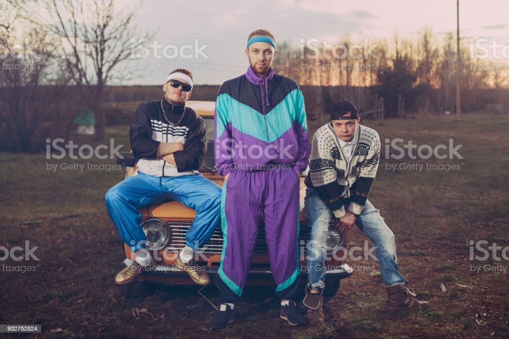 Three friends in the style of the nineties are about orange old car, stock photo
