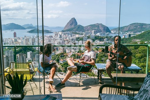 Elevated view of Rio de Janeiro cityscape, man playing guitar with two friends relaxing and listening in sunlight
