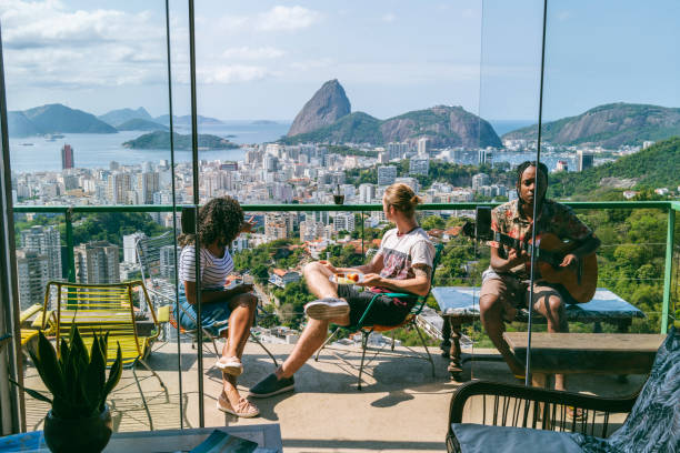 Three friends on balcony with views of Sugarloaf Mountain stock photo