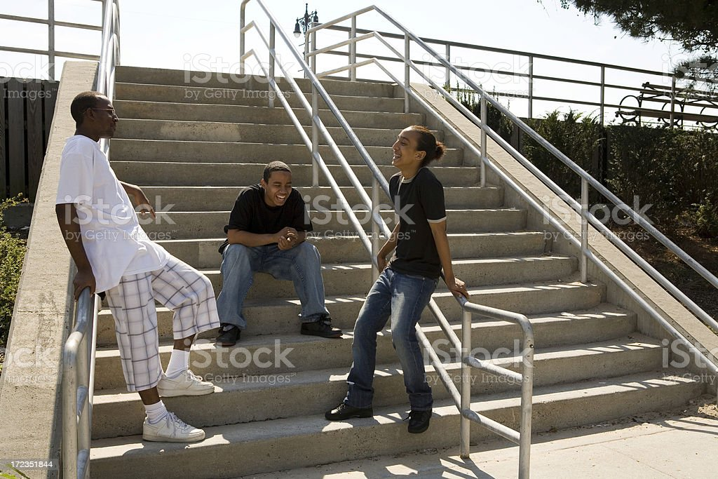 Three friends on stairs talking royalty-free stock photo