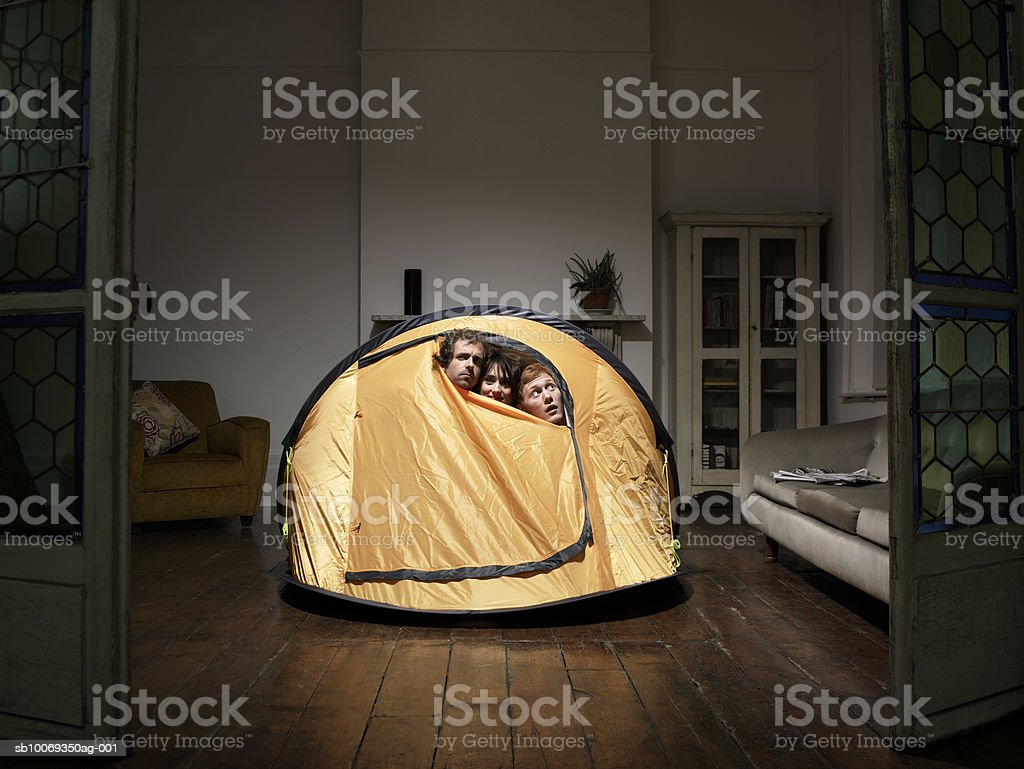 Three friends peering from tent in living room 免版稅 stock photo
