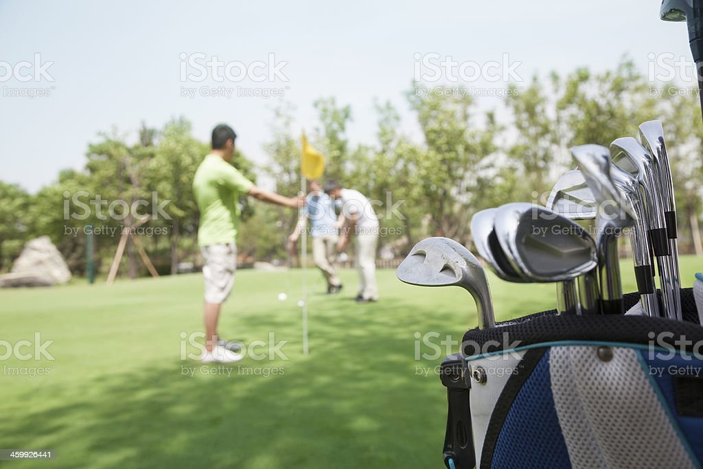 Three friends playing golf, focus on the  caddy stock photo