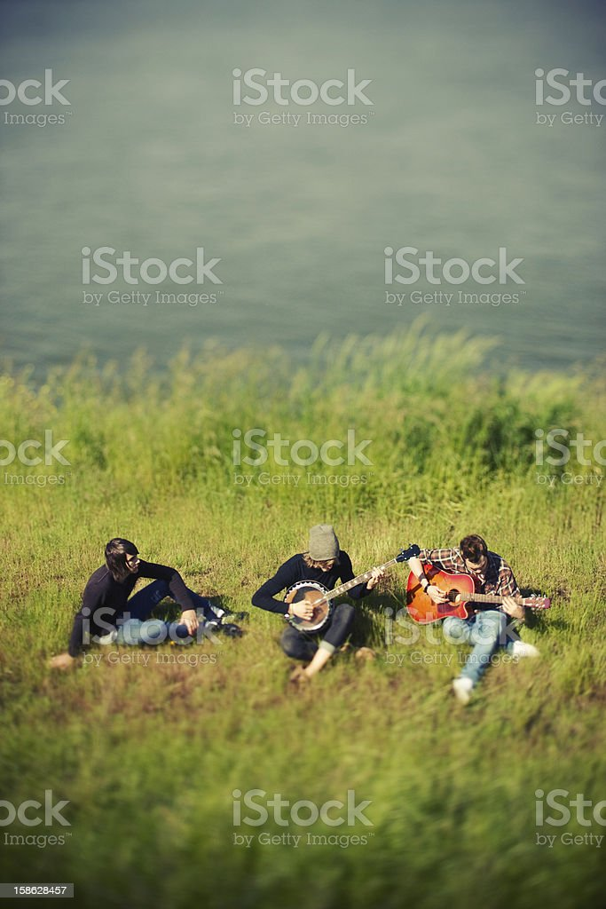 Three Friends Playing Instruments in the Grass stock photo