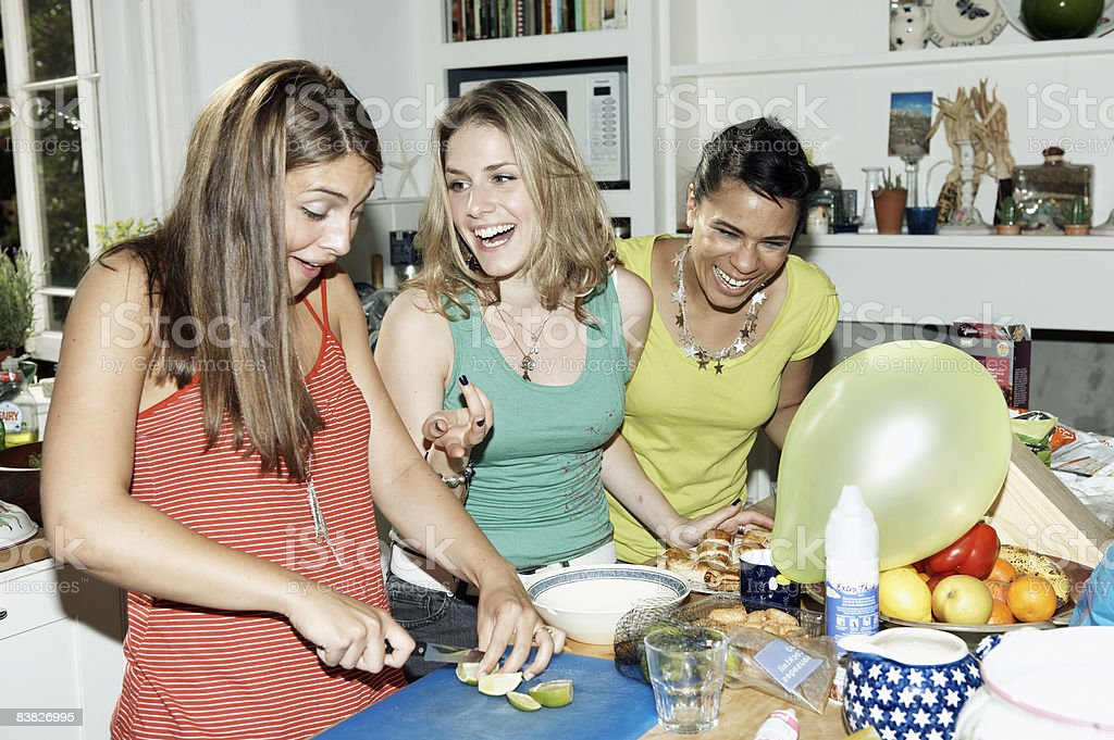 Three friends preparing food for party royalty free stockfoto