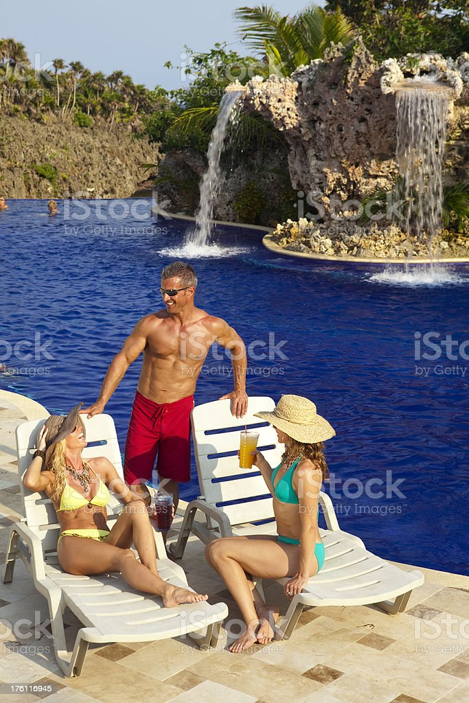 Three friends relaxing and conversing on vacation by the pool royalty-free stock photo