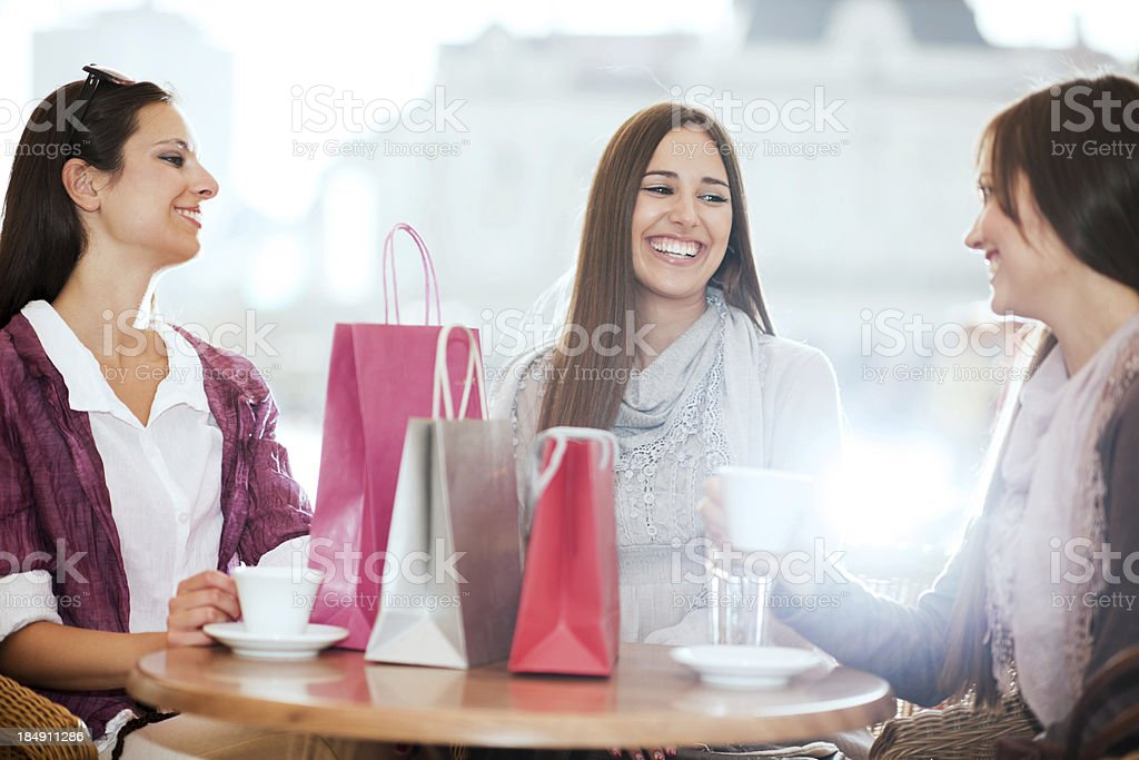 Three friends sitting in a cafe after shopping. royalty-free stock photo