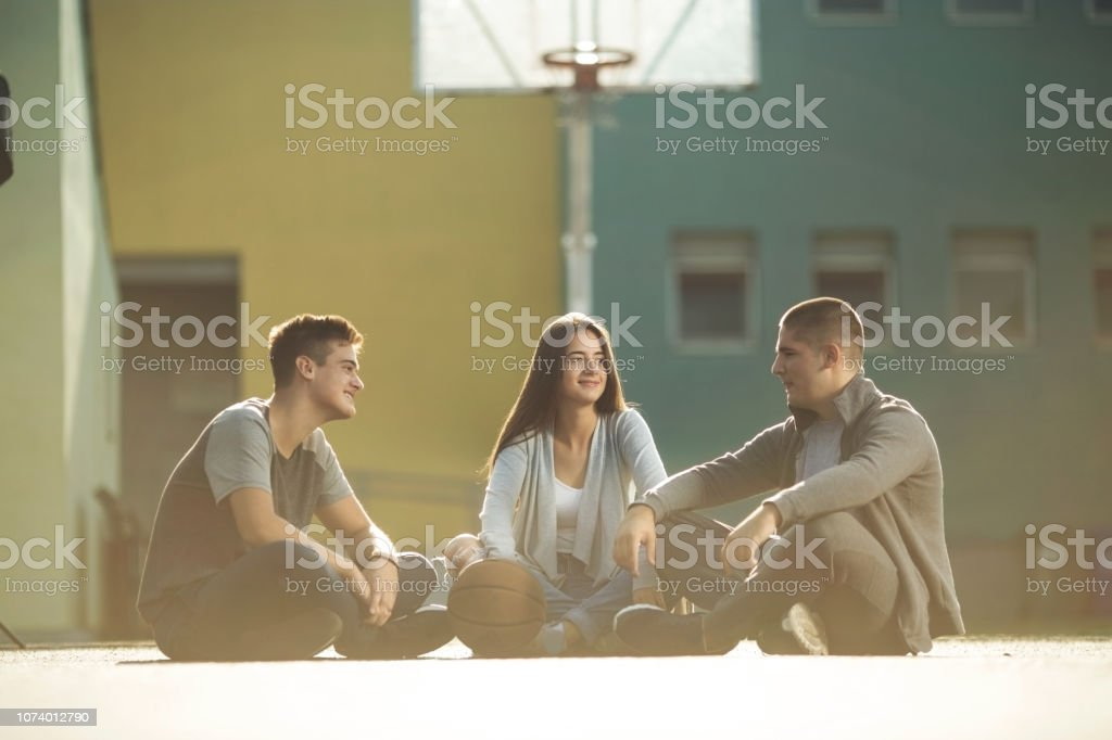 Three friends sitting on the basketball court stock photo