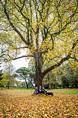 Three friends sitting underneath large tree in Autumn