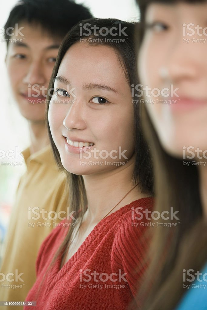 Three friends smiling, focus on woman in middle, portrait, close-up royalty-free stock photo