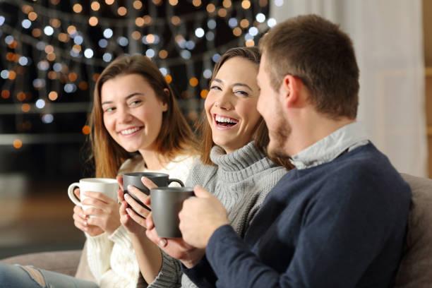 drie vrienden praten en lachen in de nacht thuis - family winter holiday stockfoto's en -beelden
