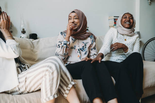 Three friends talking together sitting on the sofa at home Three friends talking together sitting on the sofa at home islam stock pictures, royalty-free photos & images