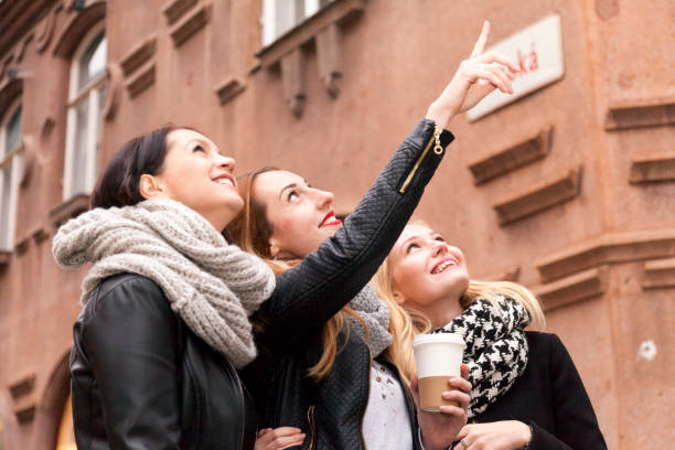 three friends tourists while sight seeing in prague three female tourists look at some towers and roof tops in the lesser town of prague's city centre wenceslas square stock pictures, royalty-free photos & images