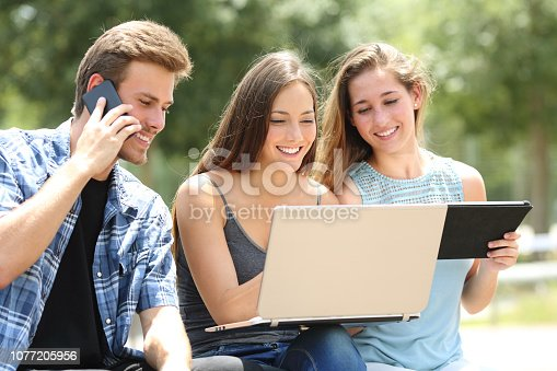 istock Three friends using multiple devices in a park 1077205956