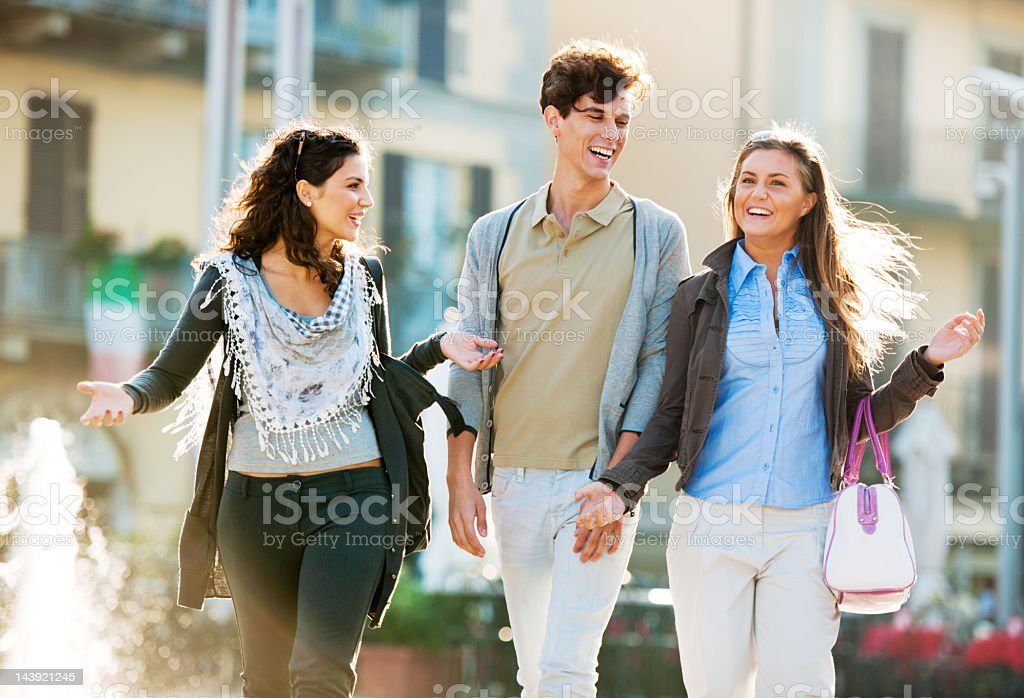 Three friends walking down the streets of a city. royalty-free stock photo