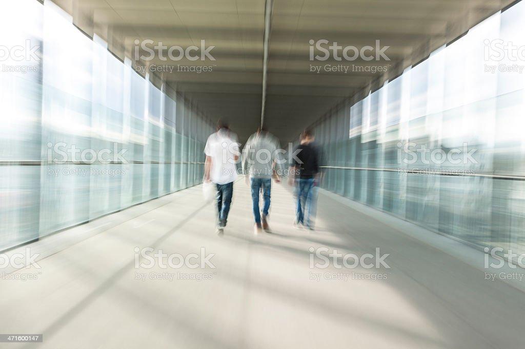 Three Friends Walking in Pedestrian Elevated Walkway royalty-free stock photo