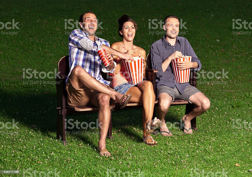 three friends watching a movie stock photo