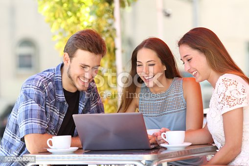 istock Three friends watching media content on laptop in a bar 1073098088