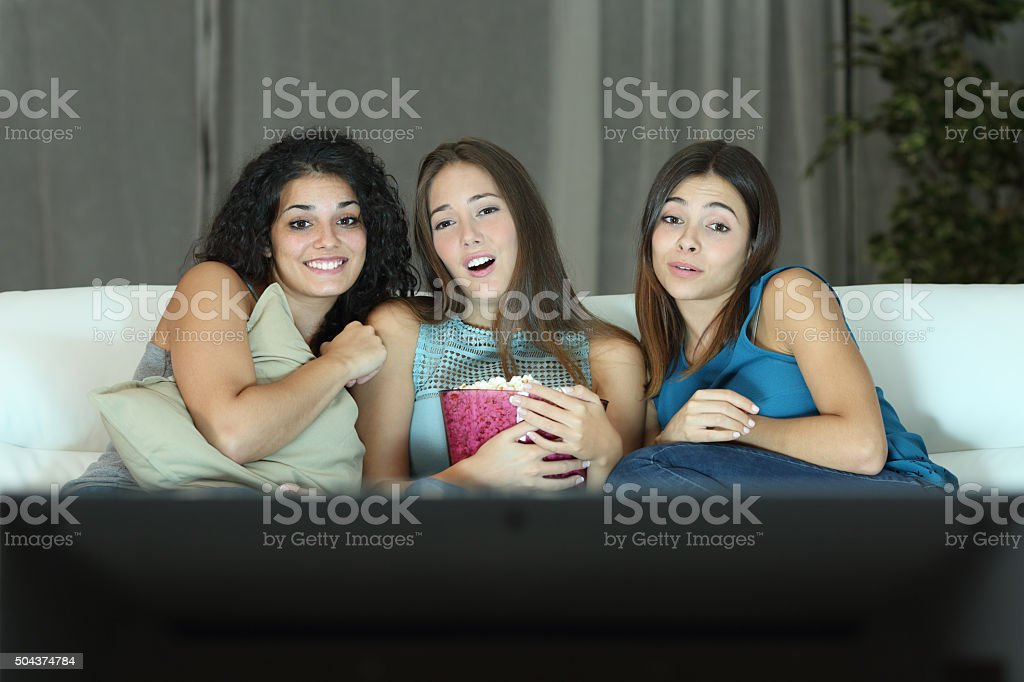 Three friends watching romantic movie on tv stock photo
