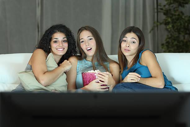 drei freunden vor dem romantischen film auf dem fernseher - mädchen night snacks stock-fotos und bilder