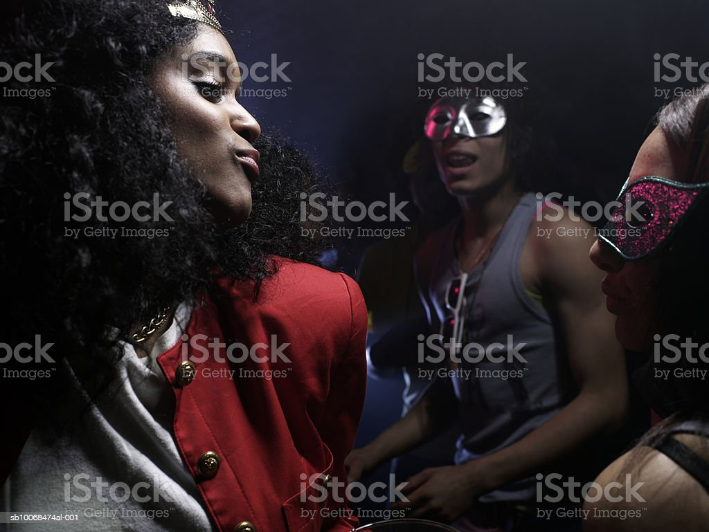 Three friends wearing costumes, dancing in night club royalty free stockfoto