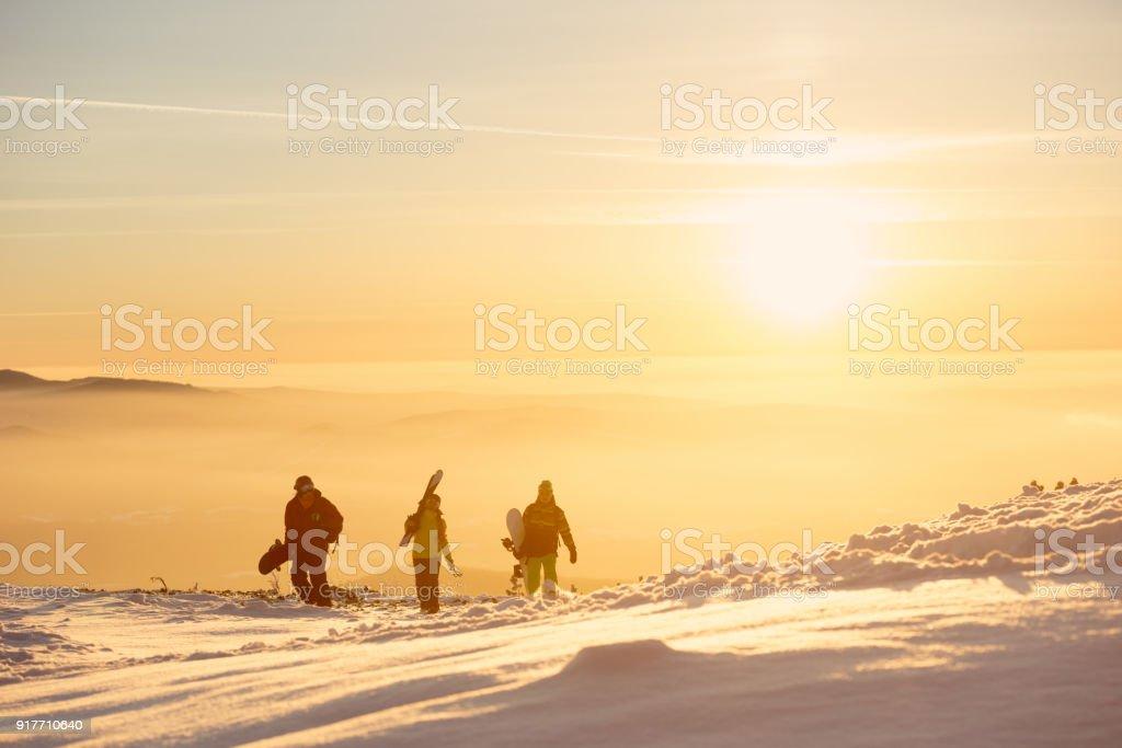 Tres amigos con esquí y snowboard en las montañas al atardecer - foto de stock