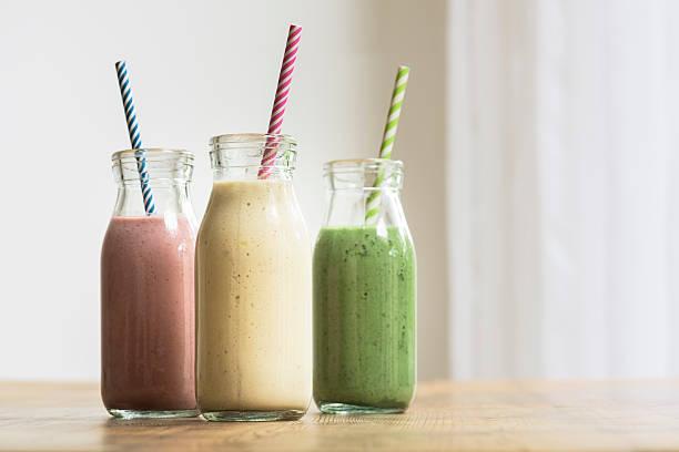 three fruit and vegetable smoothies in glass bottles with straws - diät shakes stock-fotos und bilder