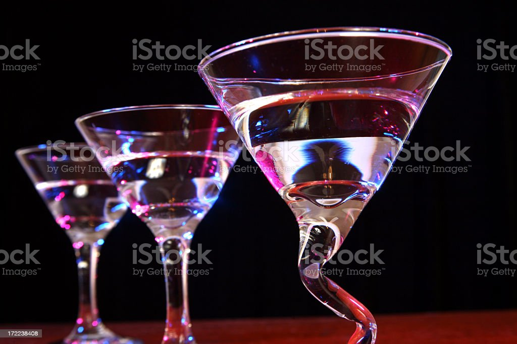 Three full martini glasses in a row. Night. Club. royalty-free stock photo