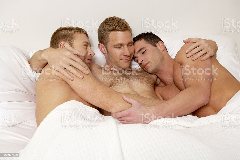 Three gay men in bed together. stock photo
