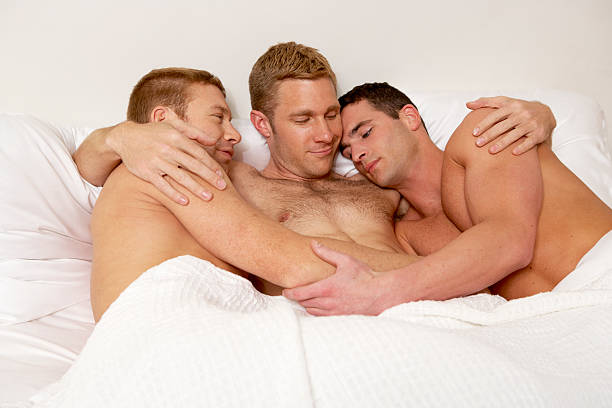 three gay men in bed together. - three people stock photos and pictures