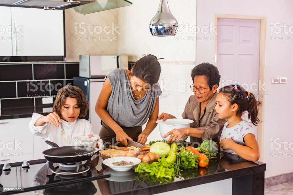 Three Generation Asian Family Cooking Healthy Food Together stock photo