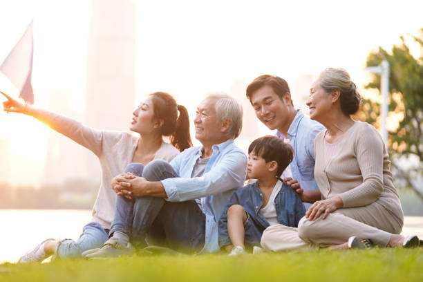three generation asian family sitting on ground watching sunset three generation happy asian family sitting on grass enjoying good time at dusk outdoors in park east asian ethnicity stock pictures, royalty-free photos & images