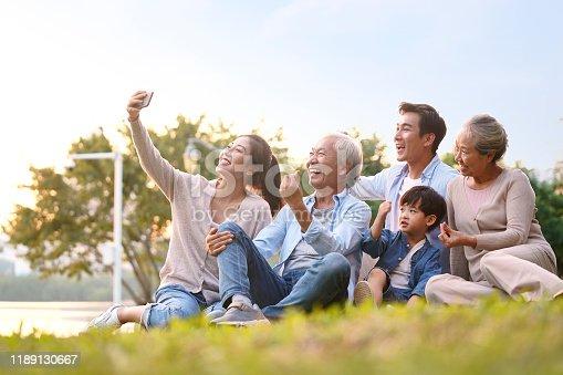 istock three generation asian family taking selfie outdoors 1189130667