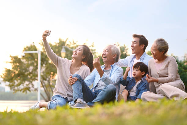 three generation asian family taking selfie outdoors three generation happy asian family sitting on grass taking a selfie using mobile phone outdoors in park old mother son asian stock pictures, royalty-free photos & images