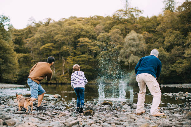 Three Generation Family are Skimming Stones Little boy is skimming pebbles on a lake with his father and grandfather. cumbria stock pictures, royalty-free photos & images