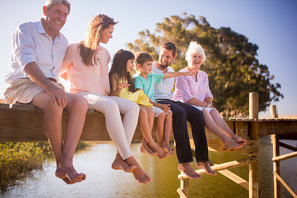 three generation family enjoying a summer vacation together - multi generation family stock photos and pictures