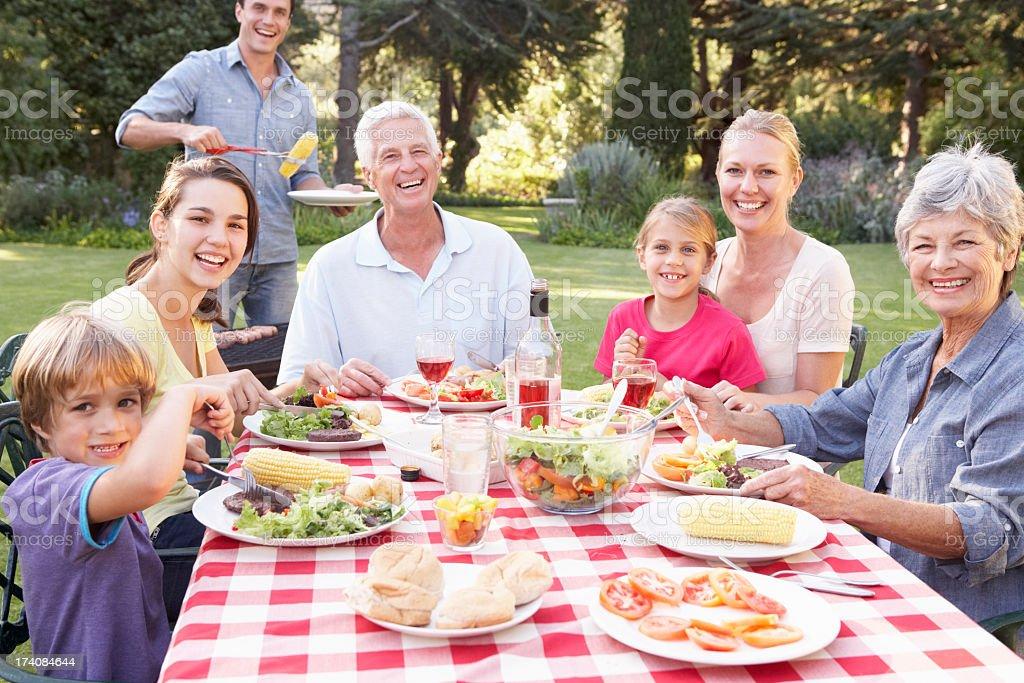 Three Generation Family Enjoying Barbeque In Garden stock photo