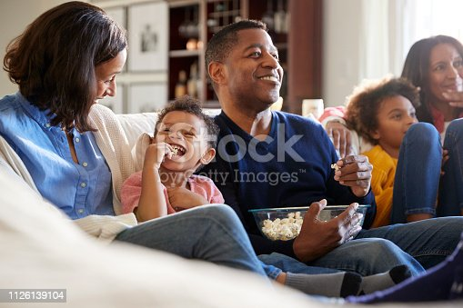 Three generation family family sitting on the sofa in living room, watching TV and eating popcorn, selective focus